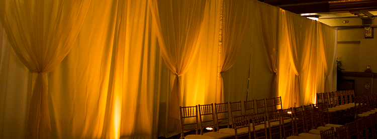 White Poly-Premier drape with Sheer Champagne Gathers for a wedding at the Hotel John Marshall. Uplights add an amber glow to the look.